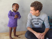 An Alternative Spring Break volunteer and young child laugh together at a Care placement abroad