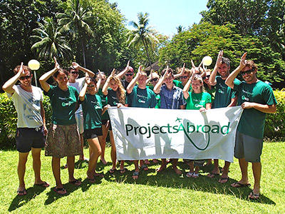 Fiji Shark Conservation volunteers hold the Projects Abroad flag at their placement.