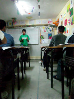 A Projects Abroad volunteer teacher in class with a group of students at her placement abroad.