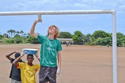Local children assist a volunteer painting a frame on a Building Project in Ghana.