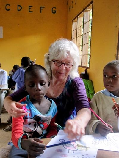 A volunteer helping a child complete their activities on a Care Project in Tanzania.