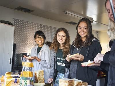 Des étudiants en chantiers jeunes bénévoles à l'étranger préparent des repas pour les membres d'une communauté