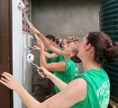 Des volontaires peignent un mur lors de leur chantier jeunes bénévoles et valident des crédits de bénévolat communautaire.