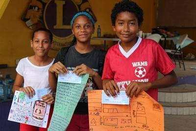 Au Belize, trois enfants reçoivent un diplôme pour leur travail bien fait