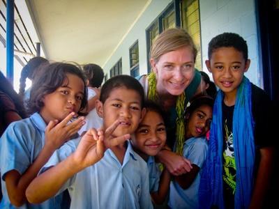 Une volontaire en mission humanitaire joue avec des enfants dans une école aux Samoa