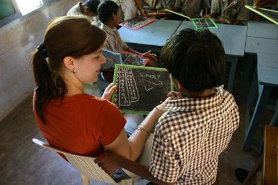 Une volontaire enseigne les mathématiques à un jeune garçon au sein d'une école bangale.