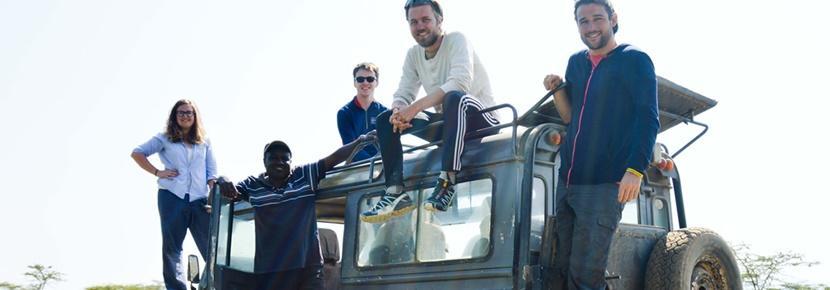 Des volontaires posent autour d'une voiture lors de leur mission humanitaire