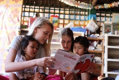 Deux jeunes volontaires lisent une histoire à des enfants dans une garderie au Cambodge