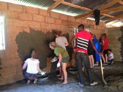 Des volontaires rénove un bâtiment lors d'une mission humanitaire et communautaire au Ghana