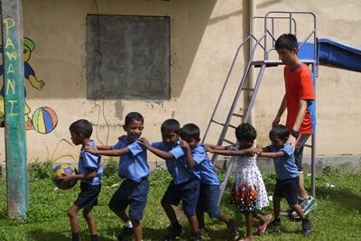 Un volontaire s'occupe d'enfants au Sri Lanka et joue avec eux dans la cour de l'école