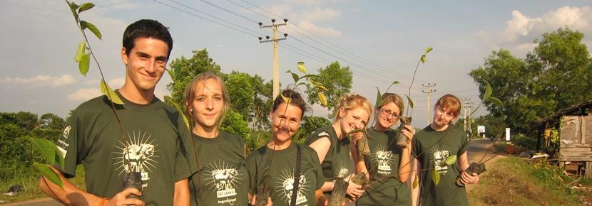 Des volontaires en voyage de groupe sur une mission d'écovolontariat posent avec des arbustes à replanter