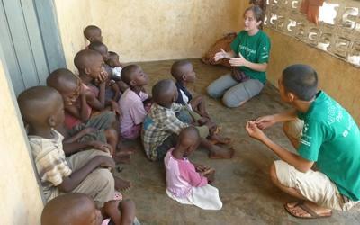 Deux volontaires parlent avec des enfants dans un orphelinat lors d'une mission en santé publique à Lomé au Togo