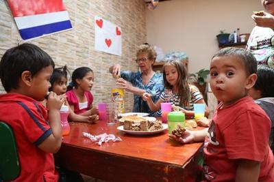 ne volontaire s'occupe du goûter d'un groupe d'enfants lors d'une mission humanitaire au Costa Rica