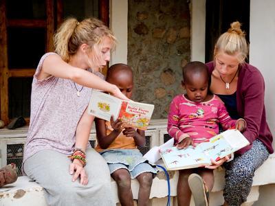 Deux volontaires lisent des livres avec des jeunes filles sur un projet d'enseignement en Tanzanie