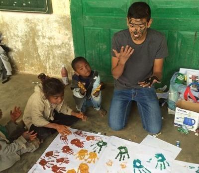 Un volontaire fait de la peinture avec des enfants lors de sa mission