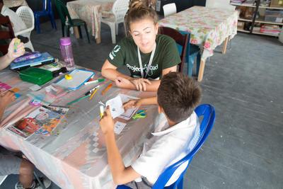 Une volontaire en mission d'enseignement pour professionnel au Belize travaille avec un enfant