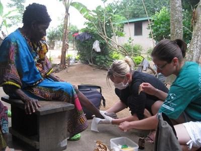 Deux volontaires aidant une dame au Ghana