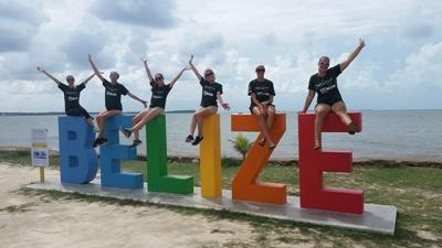 Des volontaires posent sur un signe Belize lors de leur temps libre en mission avec Projects Aborad