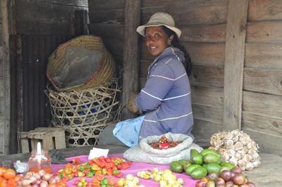 Une femme vend des fruits et légumes sur un marché à Madagascar