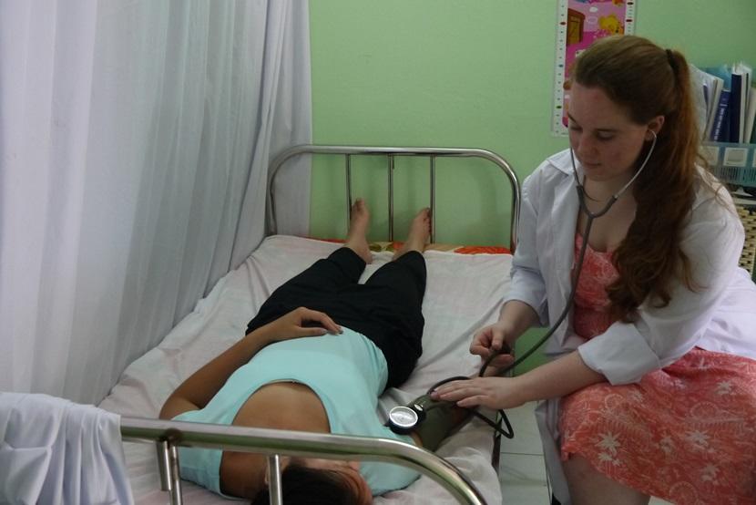 Une volontaire apprend comment examiner les signes vitaux d'un patient lors d'une mission au Vietnam