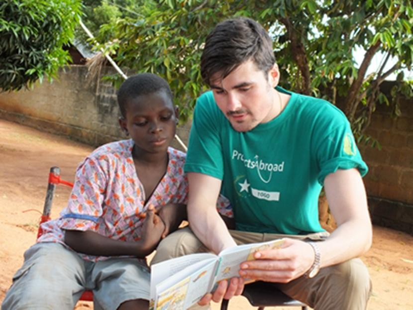 Un volontaire de Projects Abroad fait de la lecture avec un jeune garçon dans le cadre de la mission d'aide à l'enfance au Togo