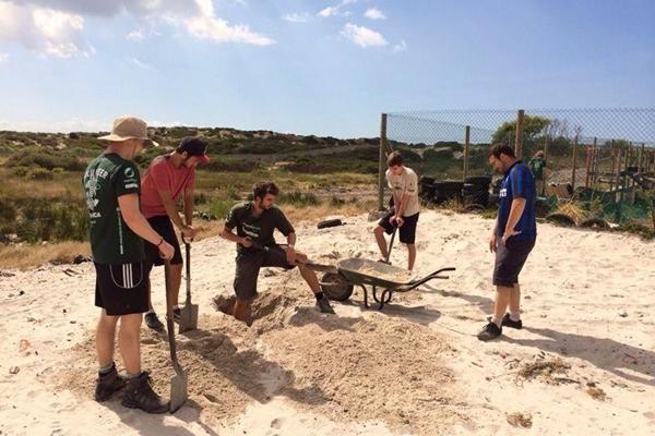 Un groupe de volontaires Projects Abroad creusent pour construire un nouveau centre communautaire au Cap, en Afrique du Sud.