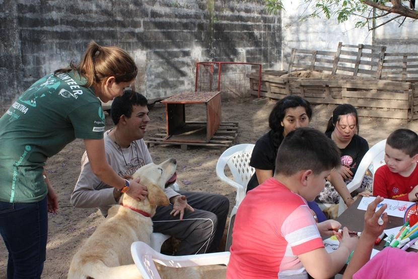 Une volontaire de Projects Abroad aide un jeune homme handicapé, lors d'une session de thérapie canine.