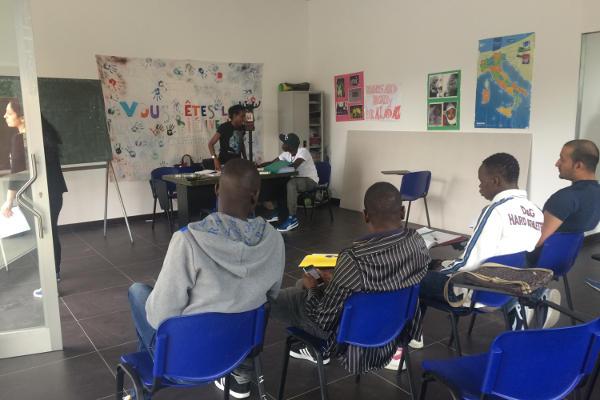 Un groupe de réfugiés et de migrants assistent à un cours de langue en Italie