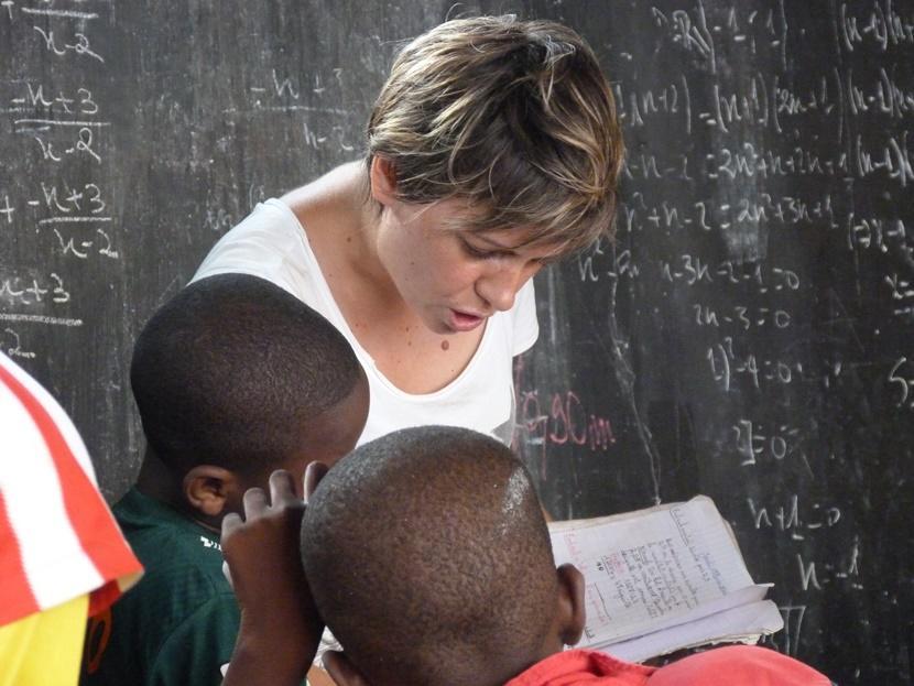 Un volontaire participant à une mission humanitaire fait de la lecture aux enfants dans un orphelinat au Togo.