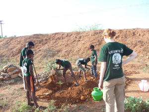 A group of volunteers observing a digging demonstration an Agriculture project