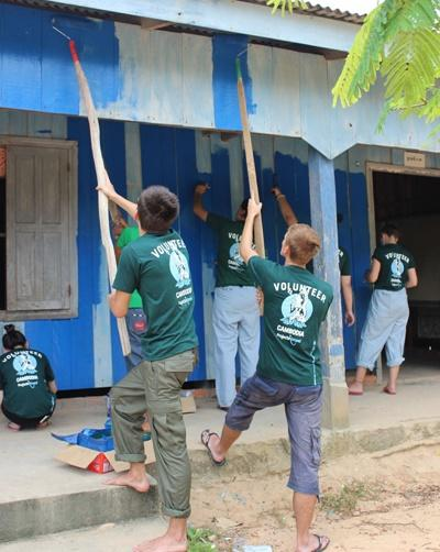 Projects Abroad volunteers paint a house as part of the contributions to the community during their gap year abroad.