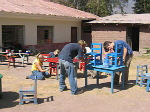 Volunteers spending their summer abroad paint furniture for a local care centre.
