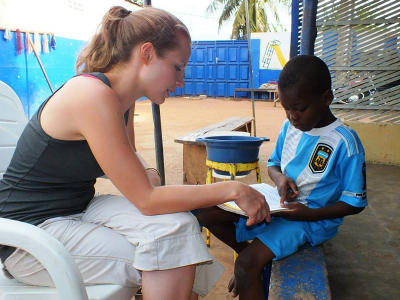 Projects Abroad volunteer from Canada reads with a Togolese child at a Care Project placement.