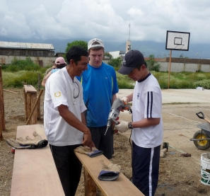 Male volunteers use power tools on the building project in Bolivia