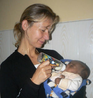 A Projects Abroad volunteer feeds a baby at  a day care centre in Ethiopia.