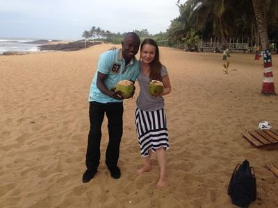 Projects Abroad staff member and volunteer enjoy coconuts on a beach in Ghana.