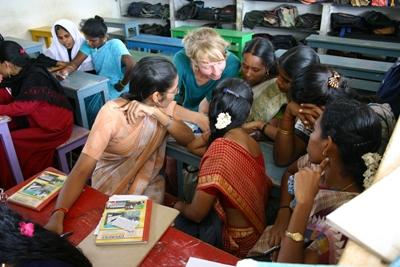 Volunteer teacher reading with students on her volunteer overseas placement