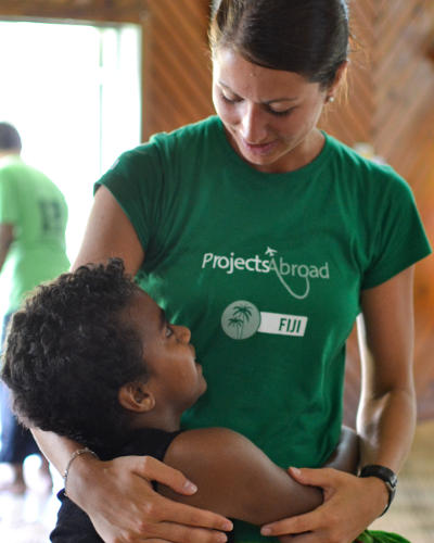 A child attending Projects Abroad's vacation classes in Fiji gives a Care volunteer a hug at a program similar to a mission trip.