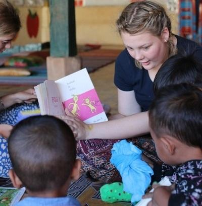 A young care and community volunteer is captured reading to the children in Cambodia