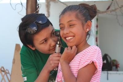 A Projects Abroad medical intern examines a child's ears during an outreach in Mexico.