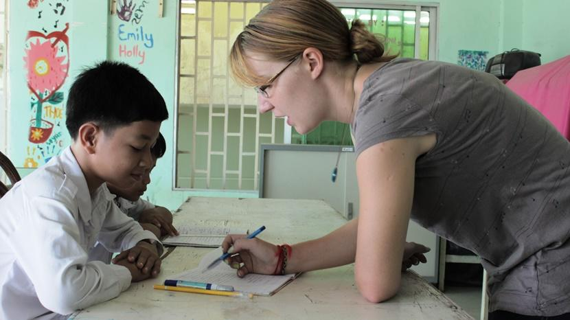 Female volunteer teaching a child in Cambodia