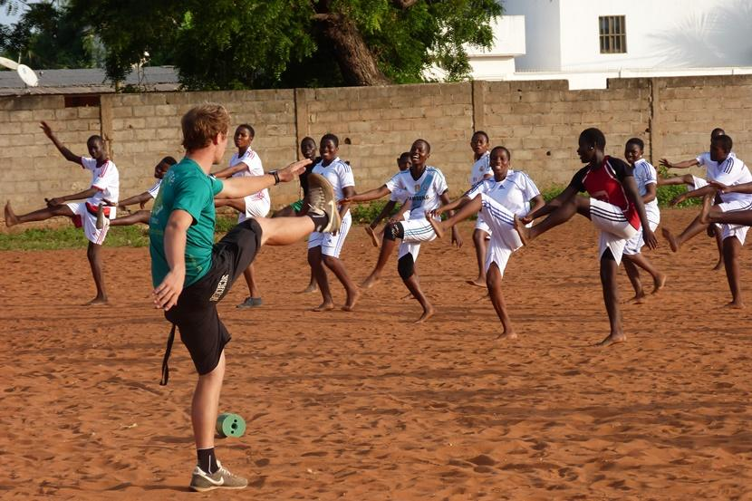 Male volunteer leads a warm up at soccer practice in Togo