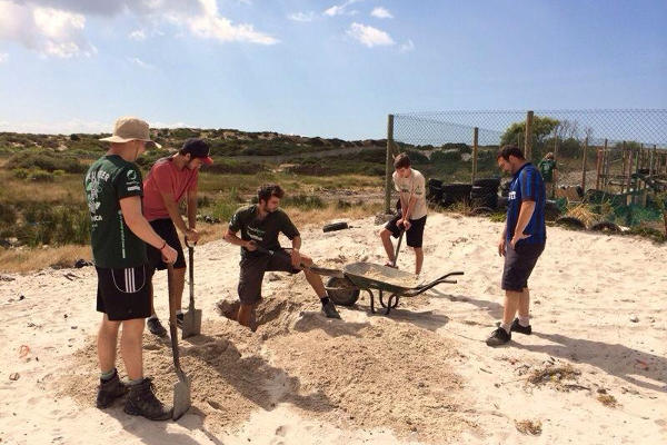 A group of Projects Abroad volunteers dig sand for building a new community centre in Cape Town, South Africa.