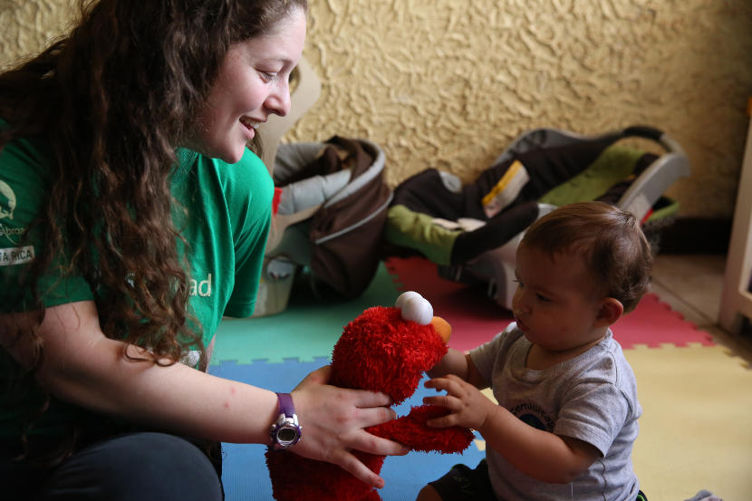 A Projects Abroad spring break volunteer plays with a young child at a Care Project in Costa Rica.