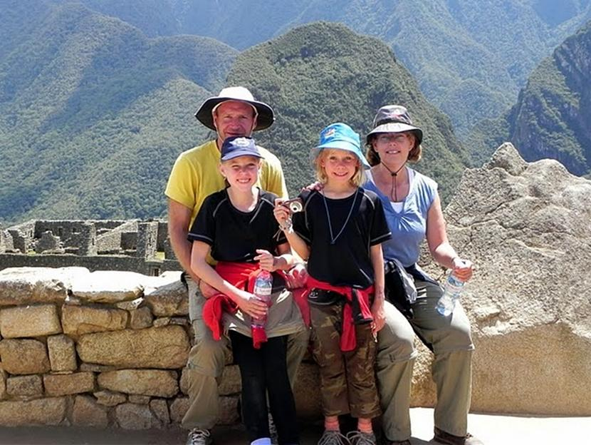 A family of four poses at the famous Machu Picchu site on their volunteer trip to Peru