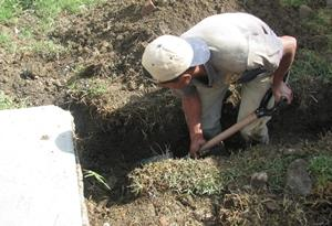 A Water & Sanitation Project volunteer digs a trench to help with clean water efforts