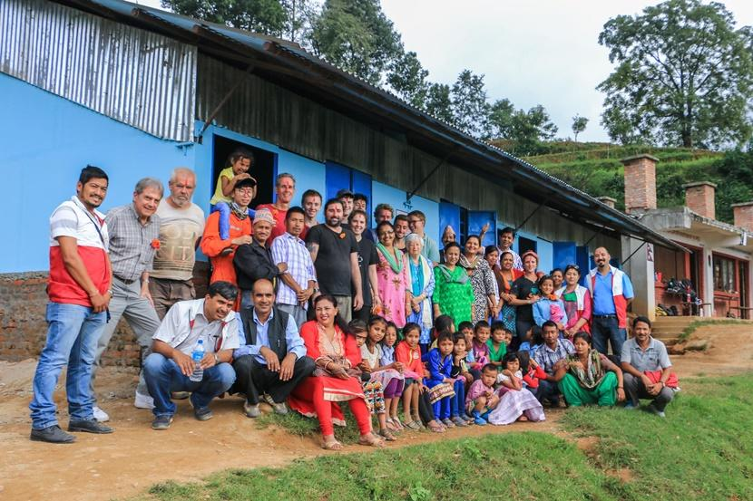 Projects Abroad staff and volunteers, along with members of the Nepal Youth Foundation, welcome students and teachers to their new classroom