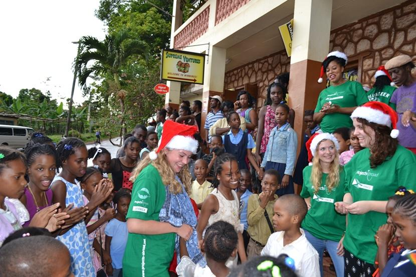 Projects Abroad volunteers play with children after distributing gifts in Jamaica for Operation Krismus Smile.