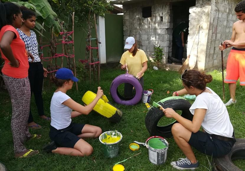 Volunteers paint a day care centre's garden colorful during their Care Project in Sri Lanka