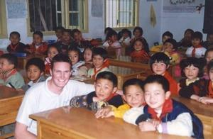 A Projects Abroad volunteer in China poses for a photo with local school children